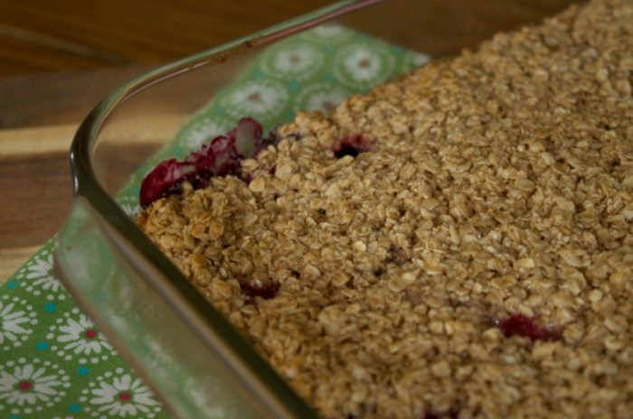 Mixed berry baked oatmeal in glass baking dish resting on green floral napkin on wooden table