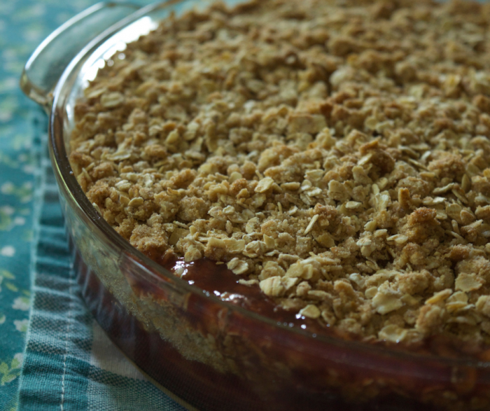 cranberry apple crisp in baking dish laying on a teal napkin