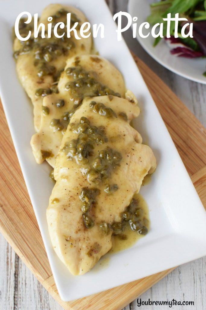 Chicken piccata laying on a white platter that is sitting on a wooden cutting board and topped with sauce and capers