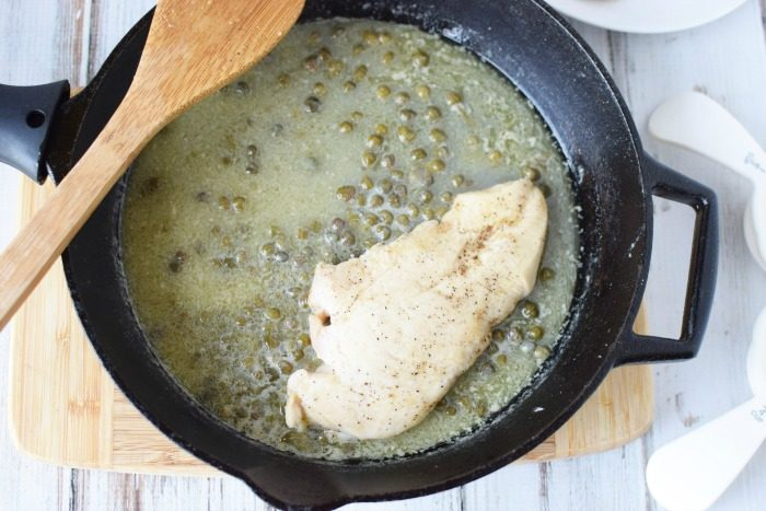 making sauce for chicken piccata in a cast iron skillet
