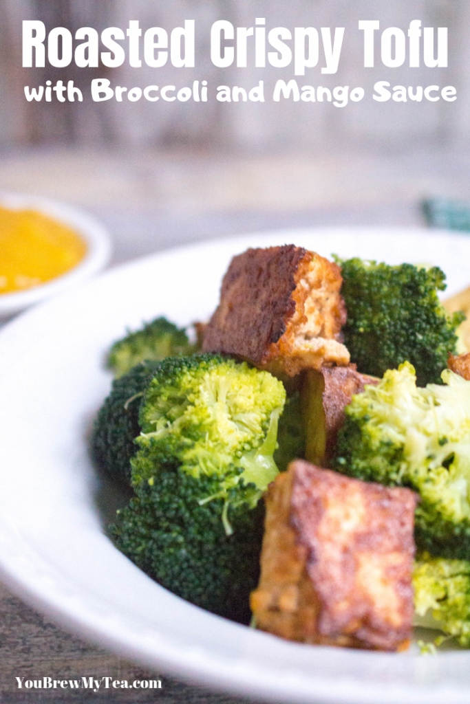 Roasted crispy tofu in a large white bowl alongside broccoli sitting on a countertop with a small bowl of mango sauce in the background