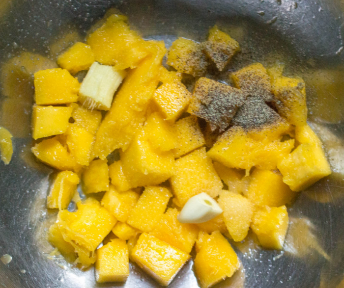 Diced mango and seasonings in a large stainless steel bowl to blend for the mango sauce that accompanies the crispy tofu and broccoli recipe