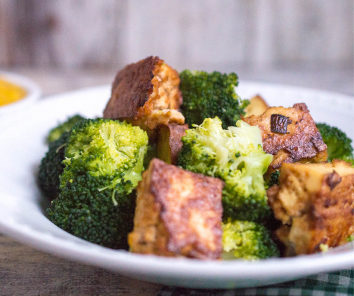 A large white plate filled with broccoli and crispy tofu sitting on a table with a small bowl of mango sauce in the background